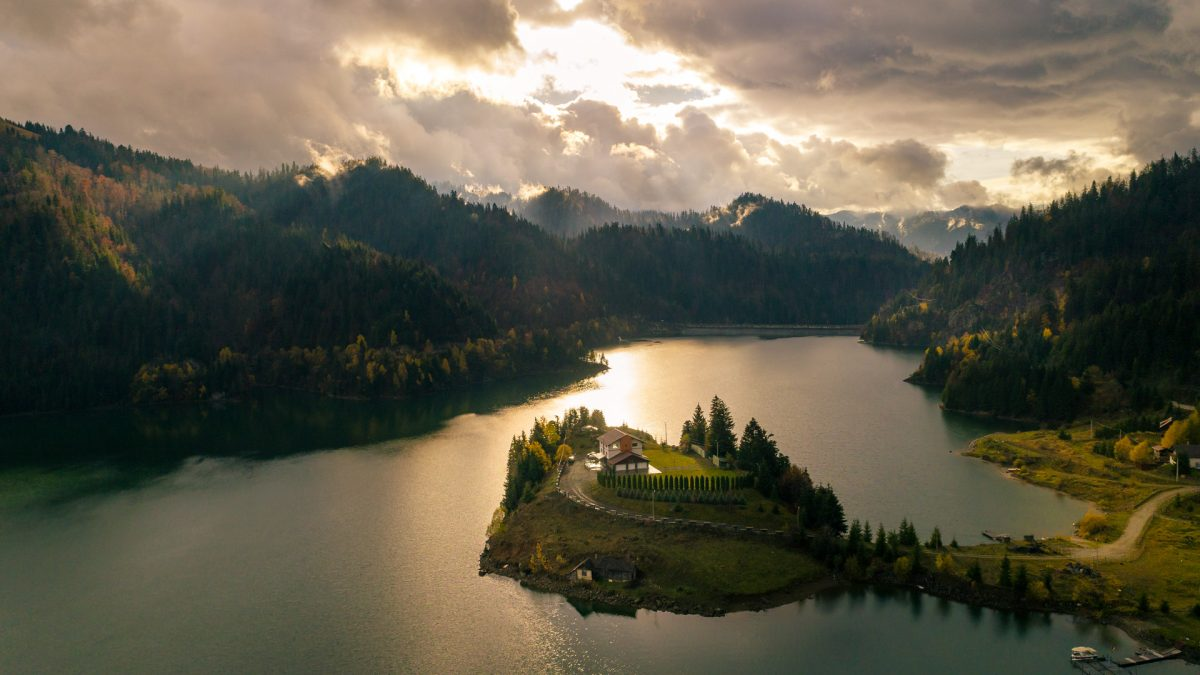 Colibita lake, surrounded by hills full of trees and the small island in the middle lighted by the sun through a small opening in the clouds