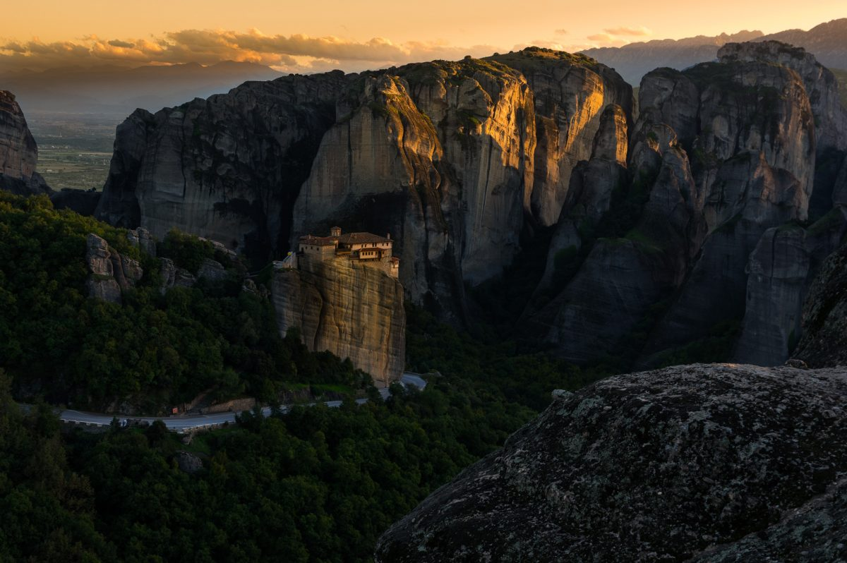 Sunset casting its light on he monastery of Roussanou which is on top of a huge monolith and the even bigger boulders on the background.