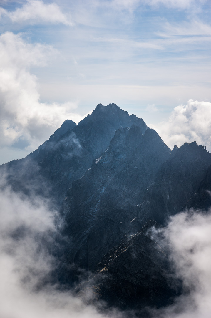 A dark mountain peak surrounded by clouds