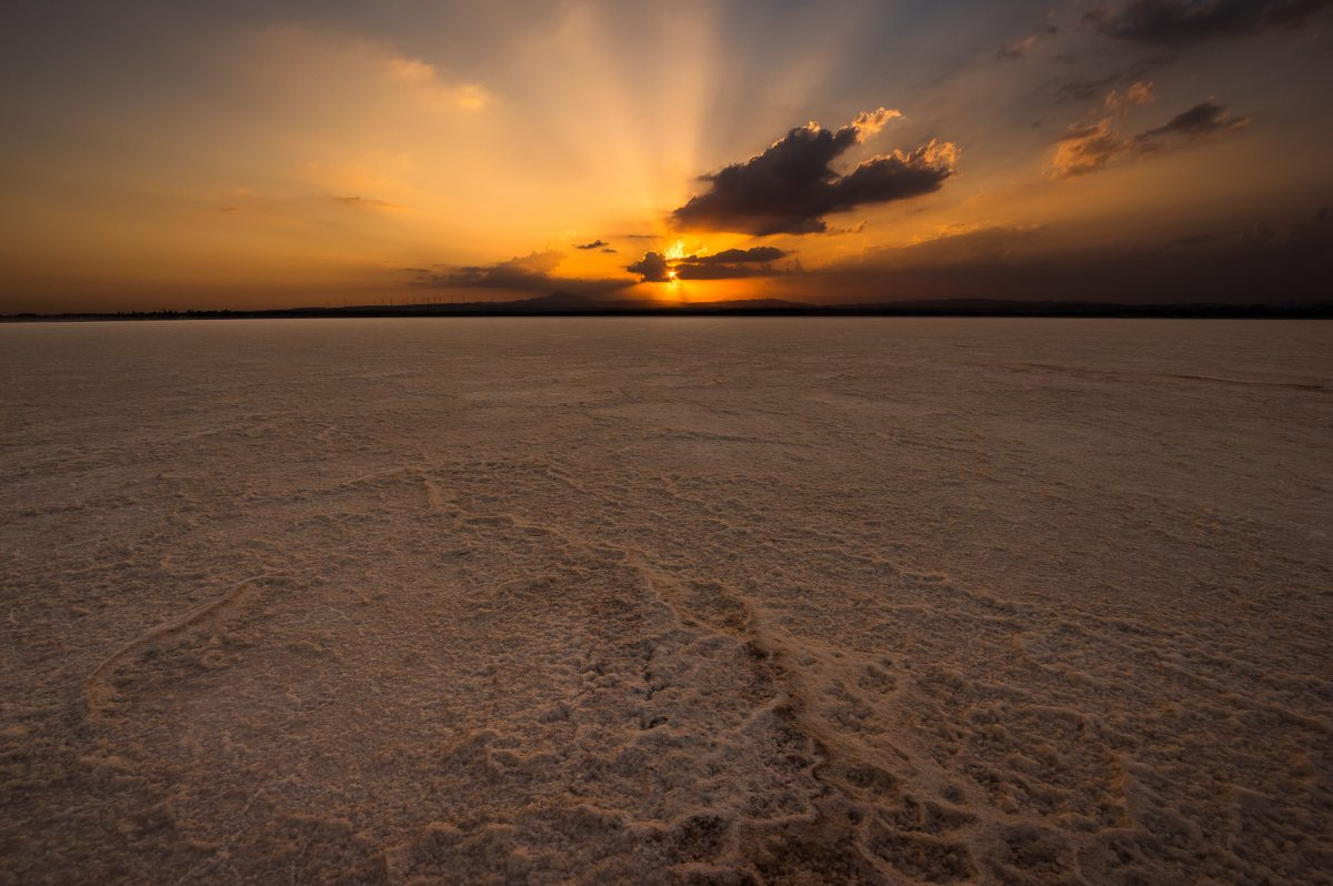 The salt lake of Larnaca during sunset, while the last rays of light, light up a few clouds on the sky