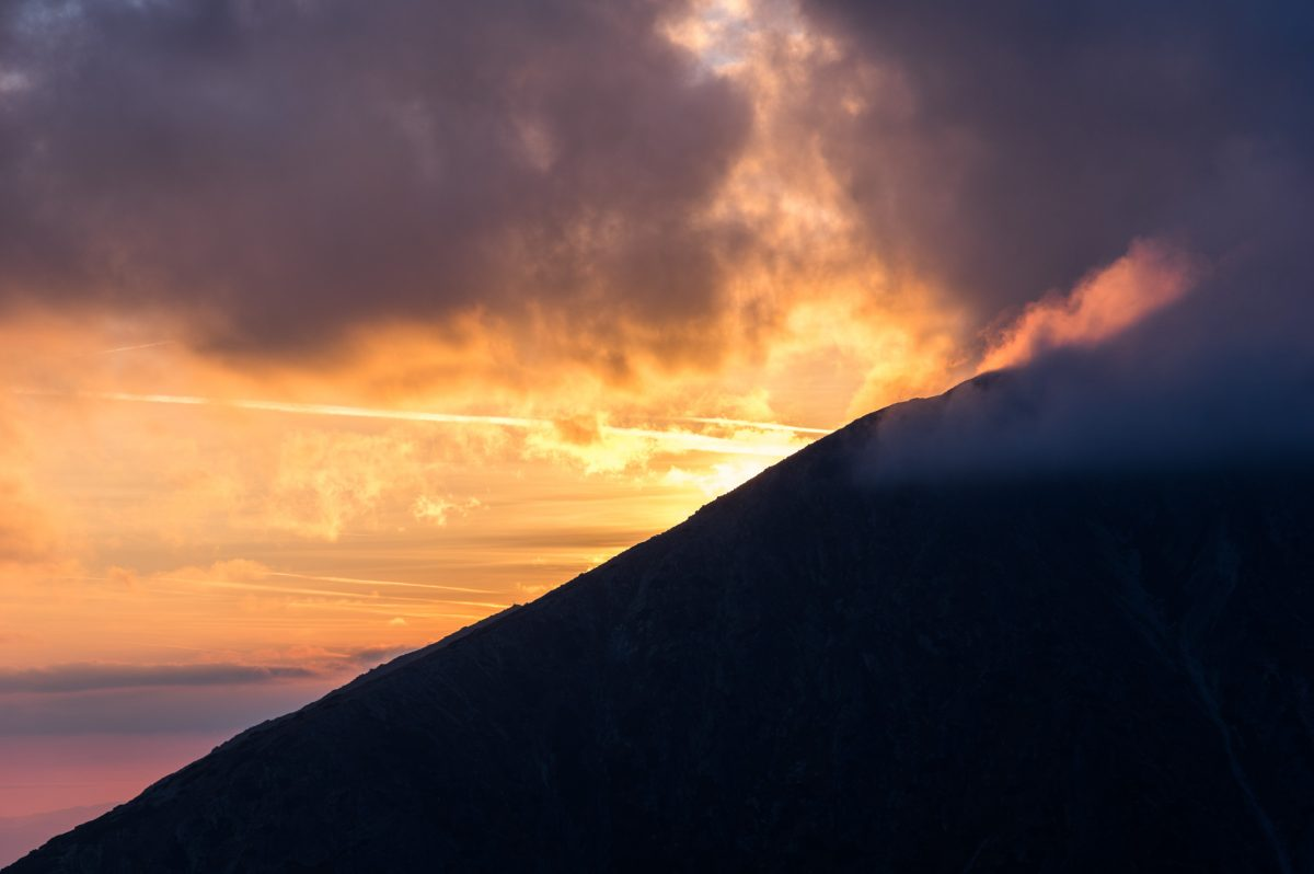 The sun setting behind a mountain slope in High Tatras