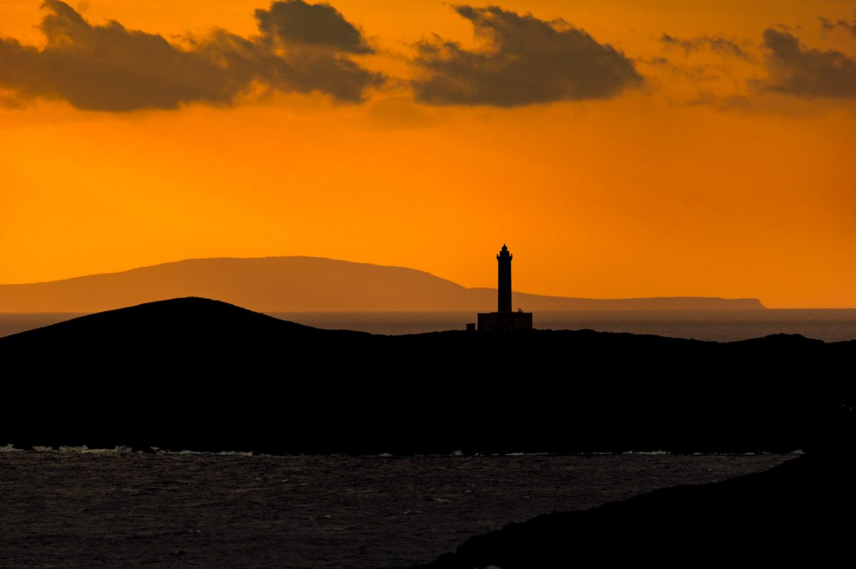 The dark sillouette of a small island with a light house and a vivid orange sky on the background