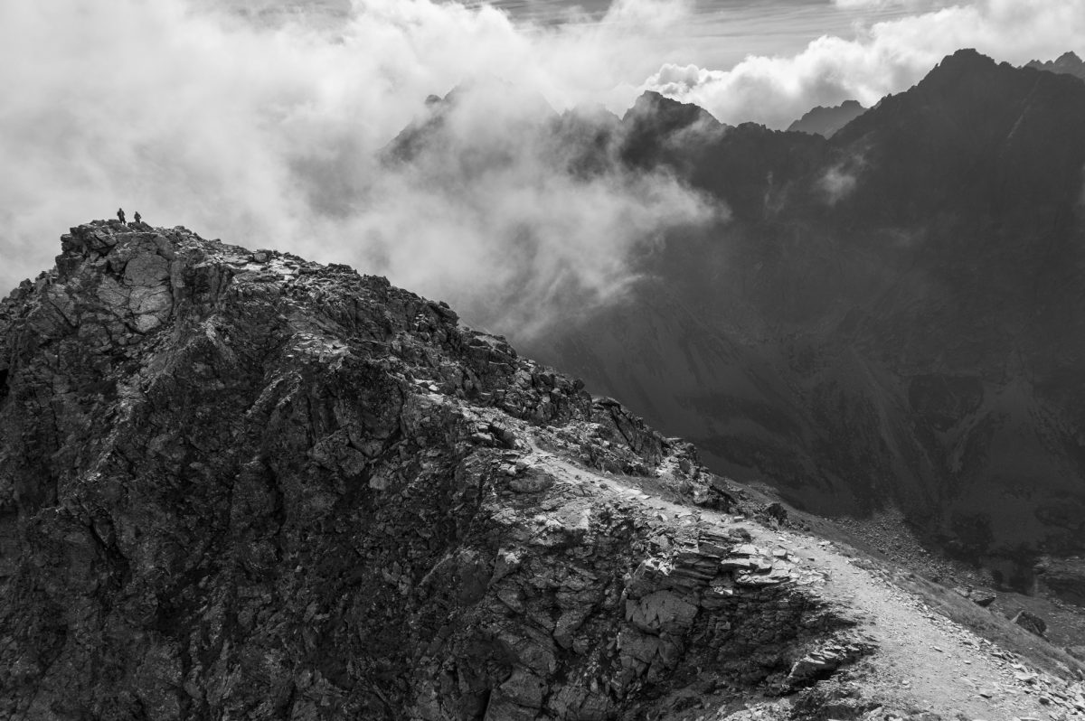 A lonely peak surrounded by other mountauns and clouds in black and white