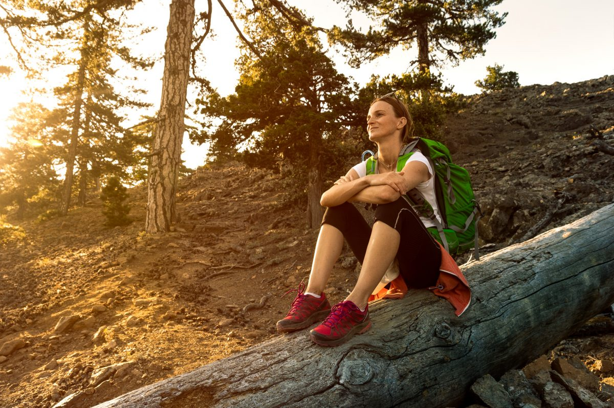 Female Hiker sitting on a fallen tree