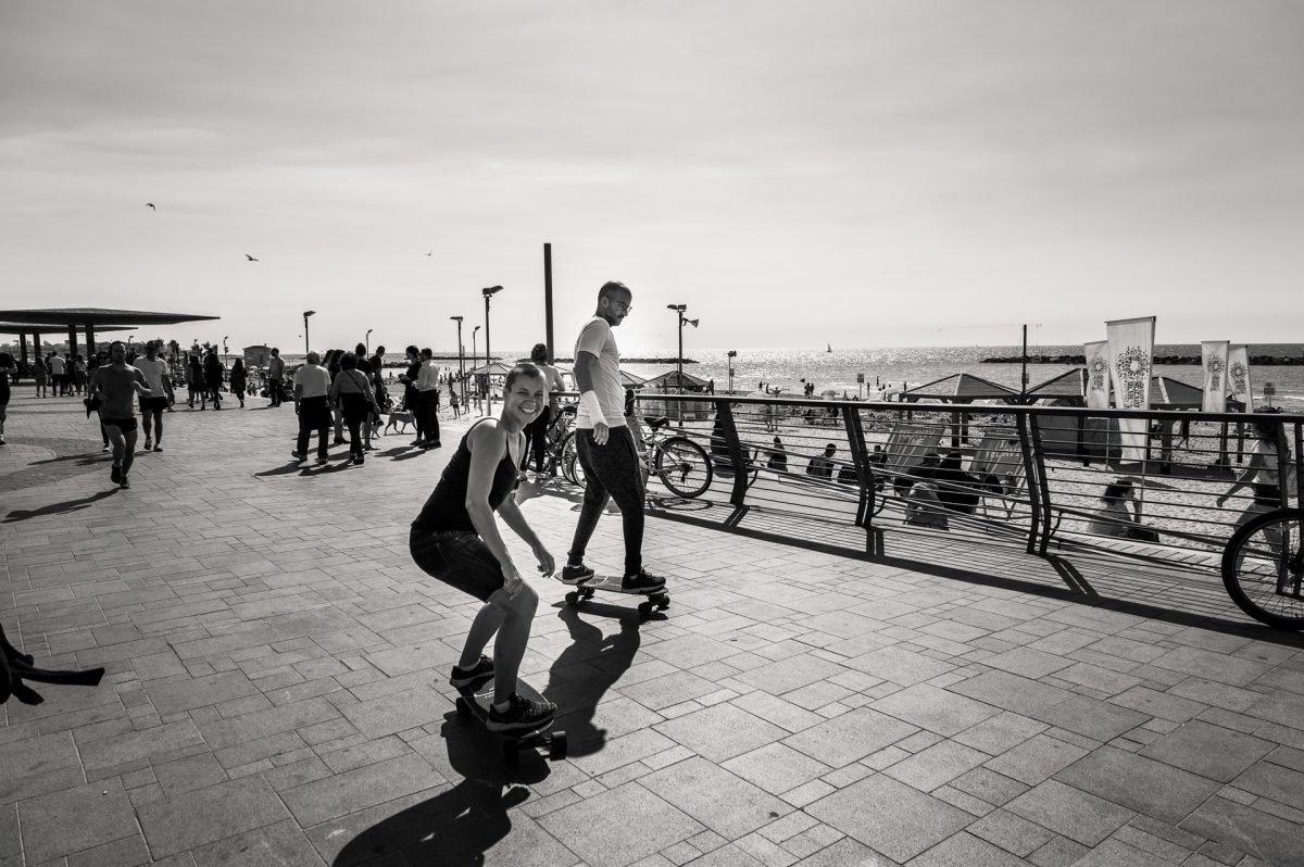 Woman and man skating along Tel Aviv promenade
