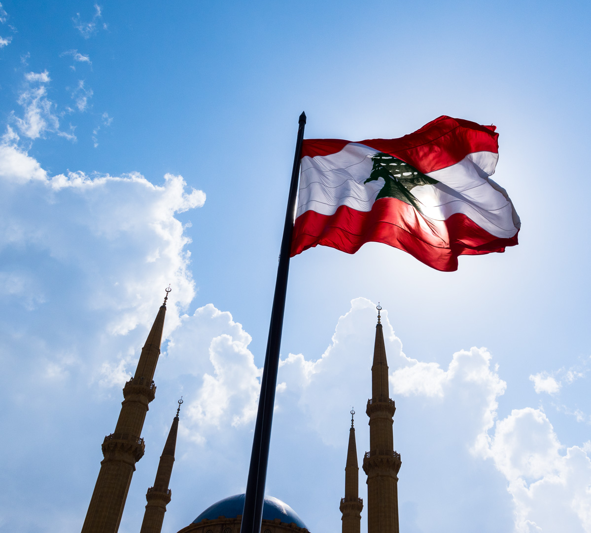 A Lebanese flag and the minarets of the blue mosque against the blue sky in Beirut, Lebanon