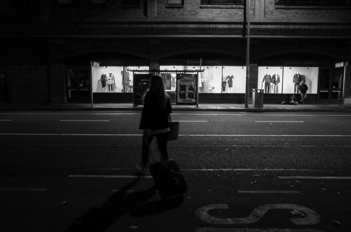 a woman crossing an avenue in the night while dragging a luggage