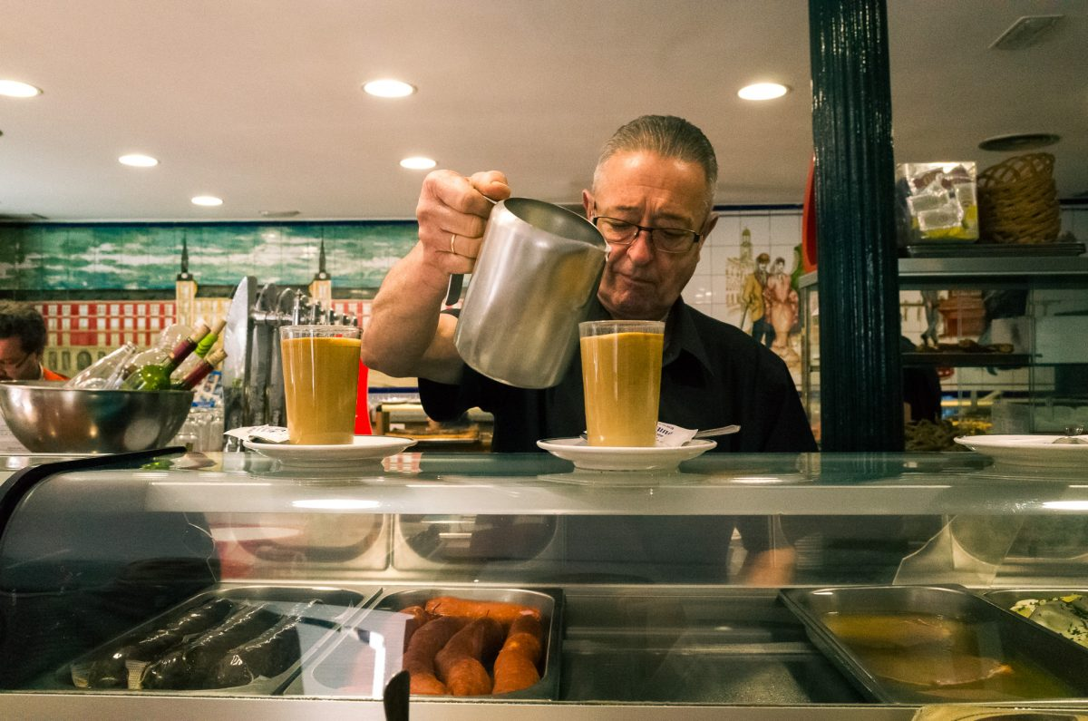 A man seving coffe in a tavern counter