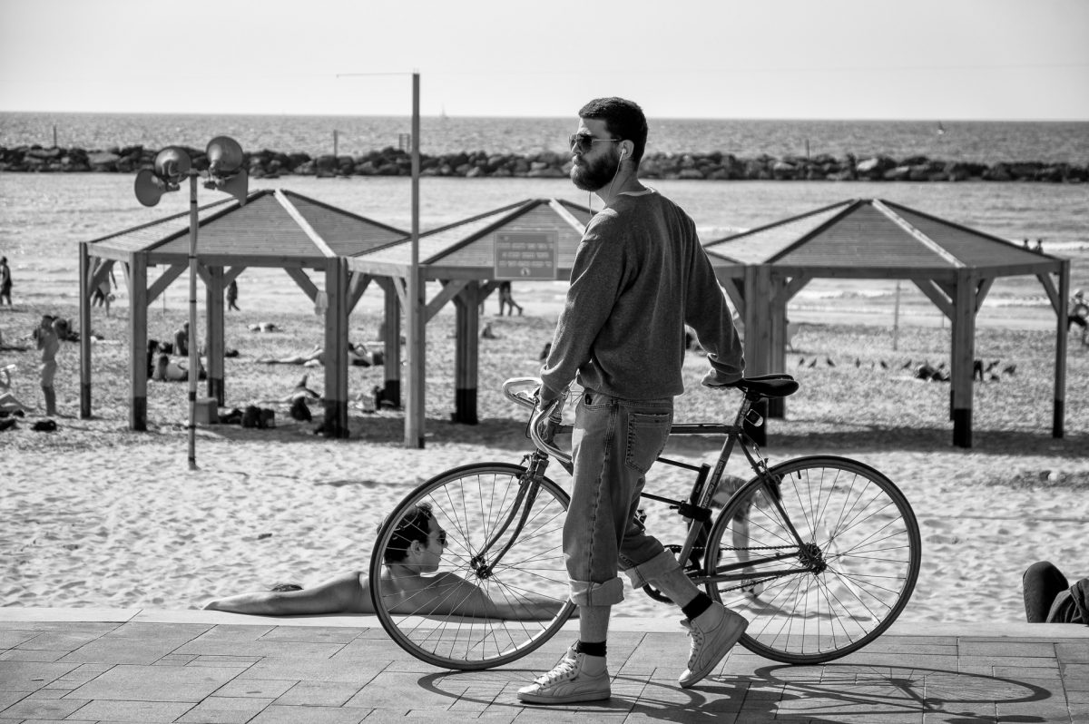 Man walking next to his bike with the beach in the background