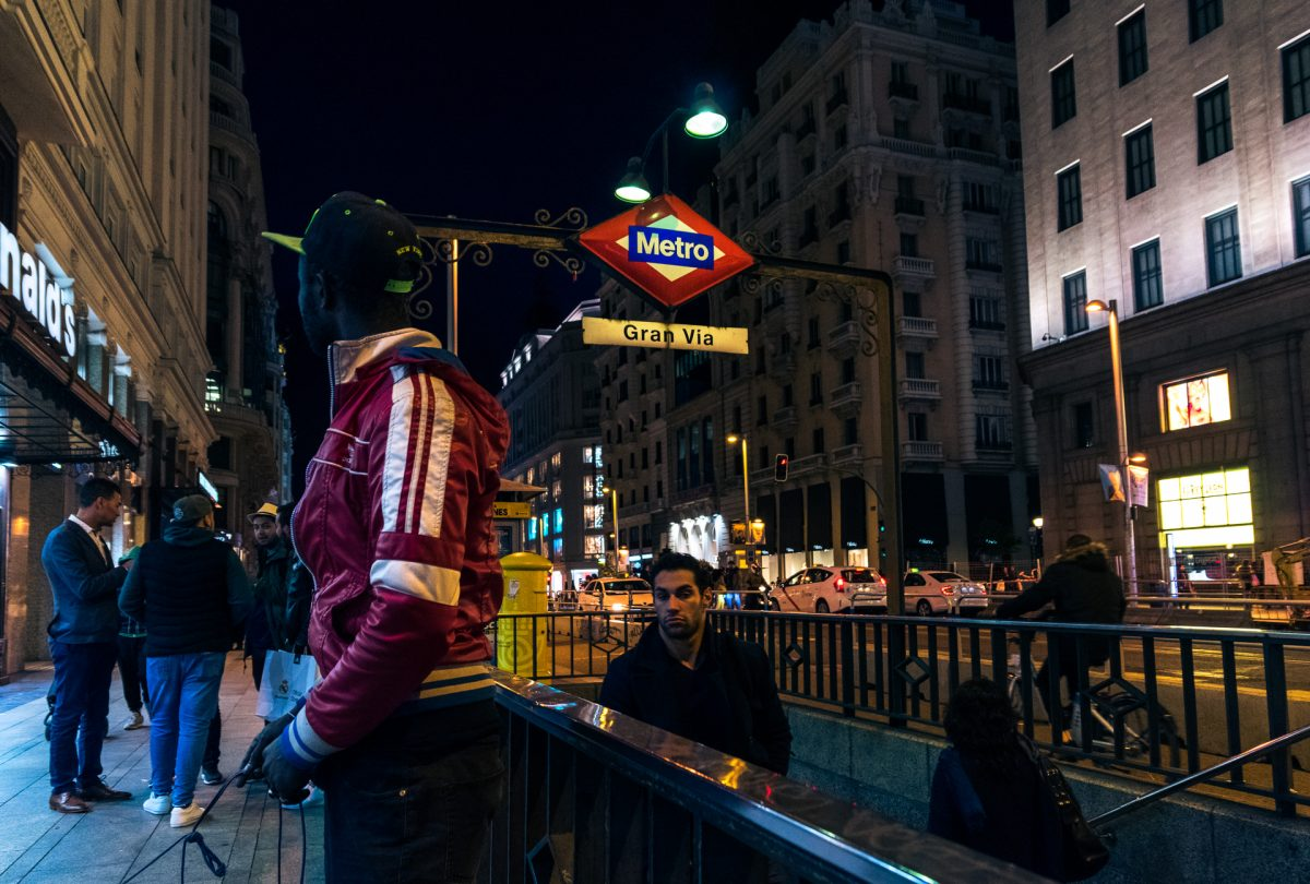 A man selling contraband outside a metro station in Madrid while looking around for police