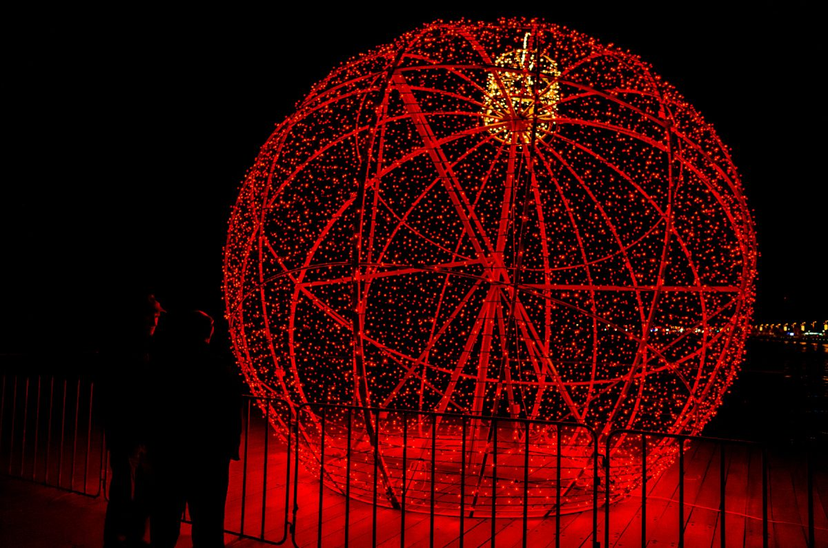 Dark figures of two men partly lighten by the strong red light of a huge christmas ball