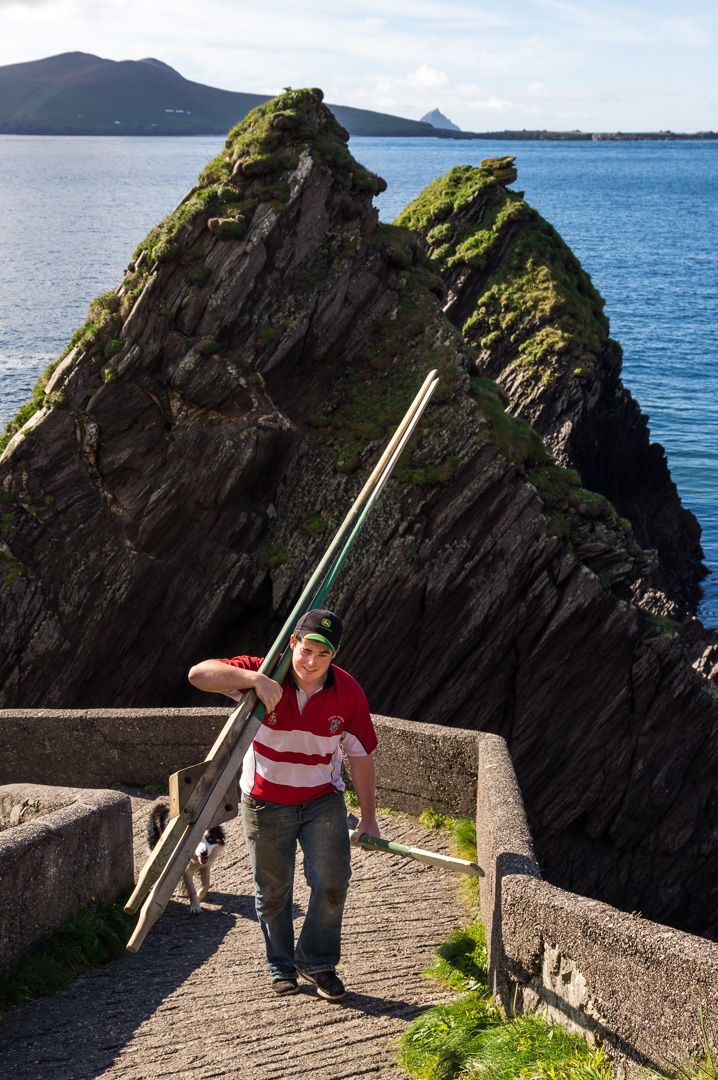 A young man carrying planks uphill on the small road leading down the Dunquin pier
