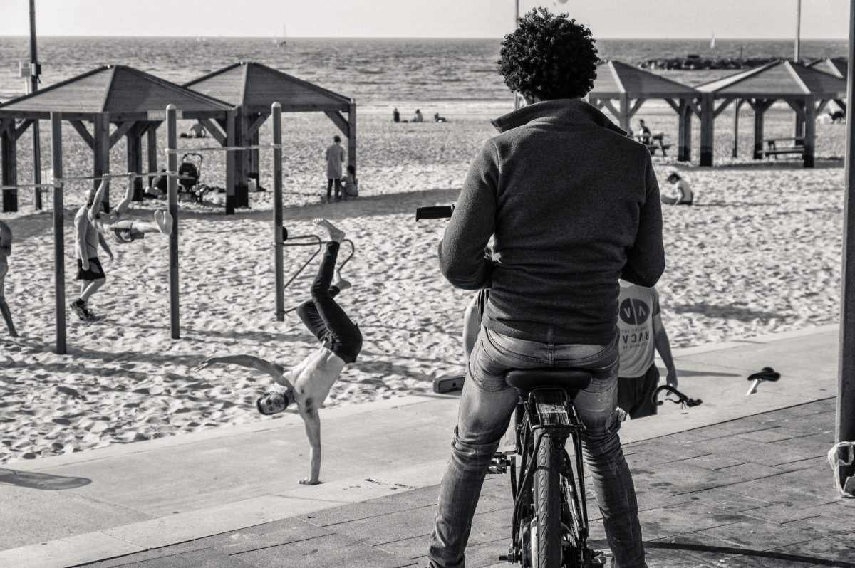 A man on a bicycle looking at people working out on the beach