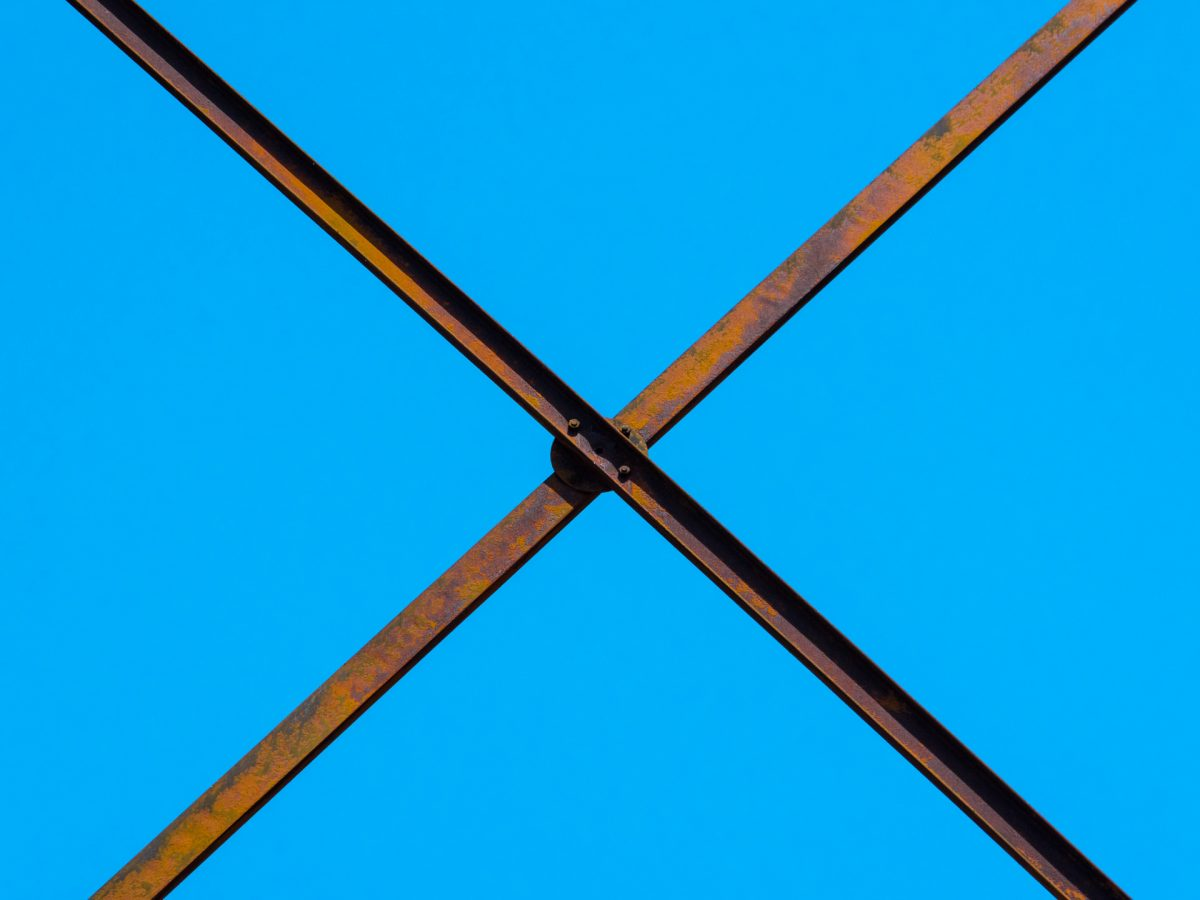 rusty iron beams forming an x against blue sky