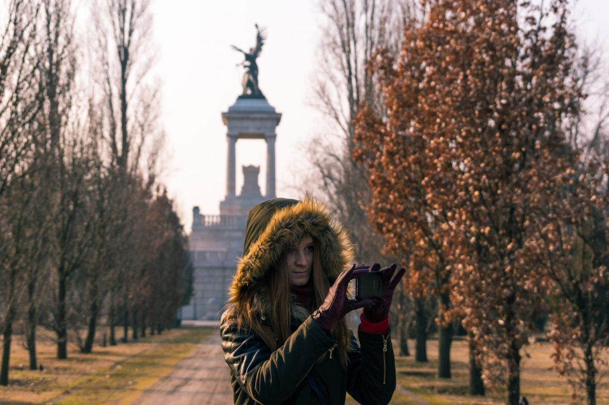 A woman taking a photo with a phone in Kerepesi cemetery, Budapest