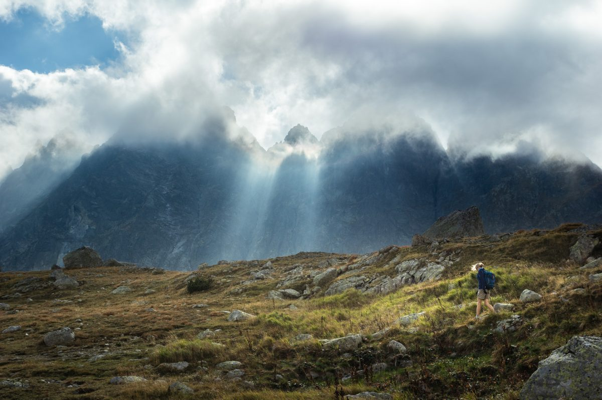 Sun coming through clouds and peaks down to a slope where a hiker is walking