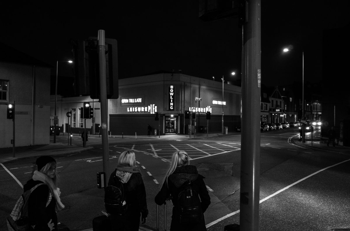 3 girls waiting to cross a big junction. There is a big bowling with neon lights across