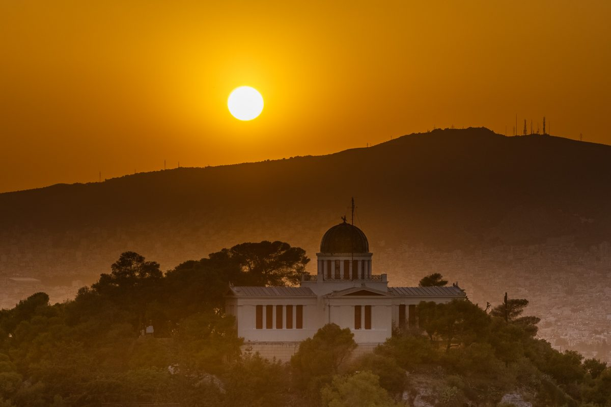 The national observatory building in Athens with the sun setting behind.