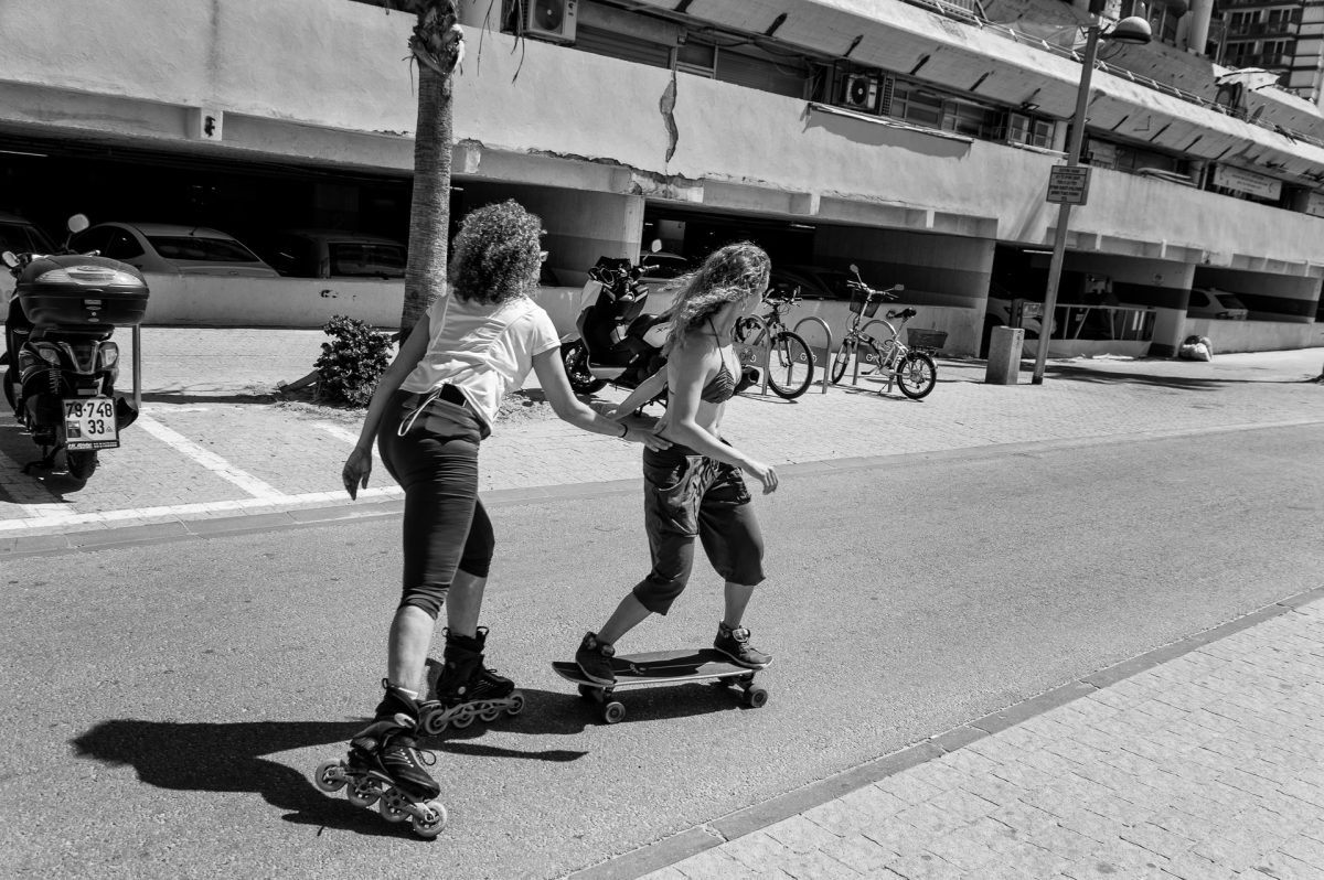 A girl on inline skates pushing another girl on skateboard