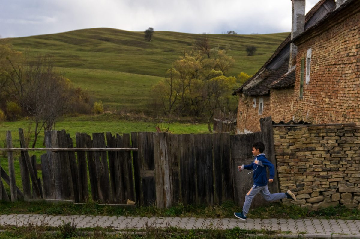 A kid running along a wooden fence somewhere in rural Romania
