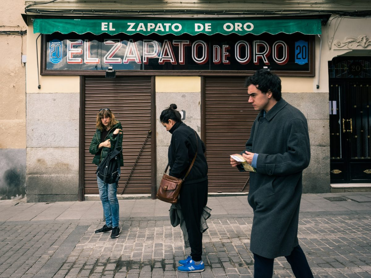 "3 people in a narrow street in front of a closed shop with a sign that reads ""El Zapato de Oro"""