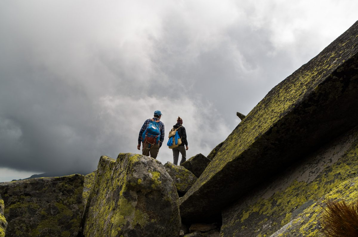 Two hikers walking on granite boulders