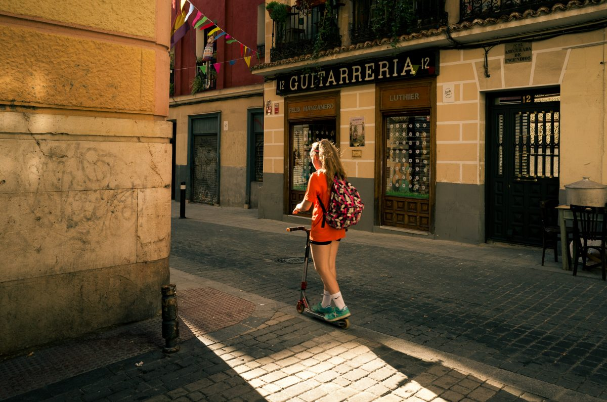 a girl with an orange t shirt and a school bag riding through a sun beam in one of madrid's narrow alleys.