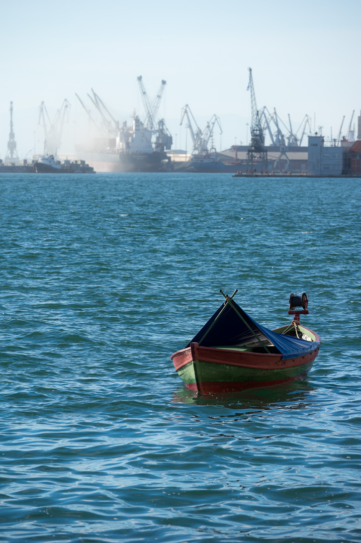 A lone boat in the sea and a big port with cranes and ships in the background
