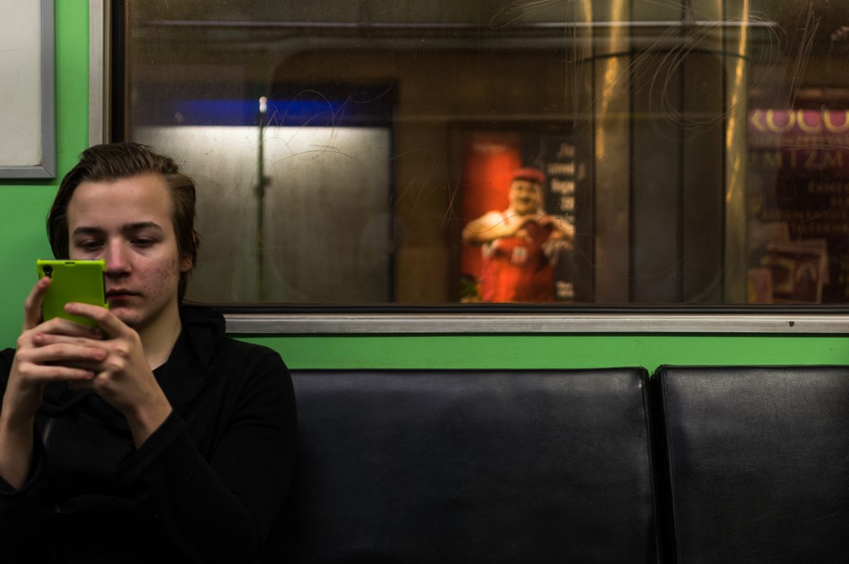 A teen looking at his lime colored phone while sitting in a metro train with lime interior walls