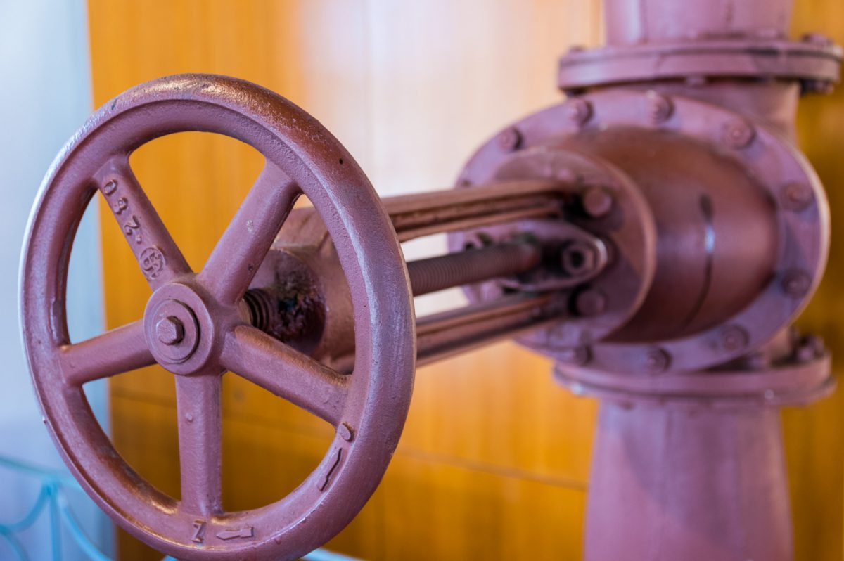 Purple-pink valve wheel against orange wall