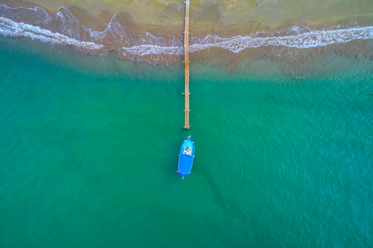 A fishing boat tied to a beach pier in Zapalo beach, Cyprus