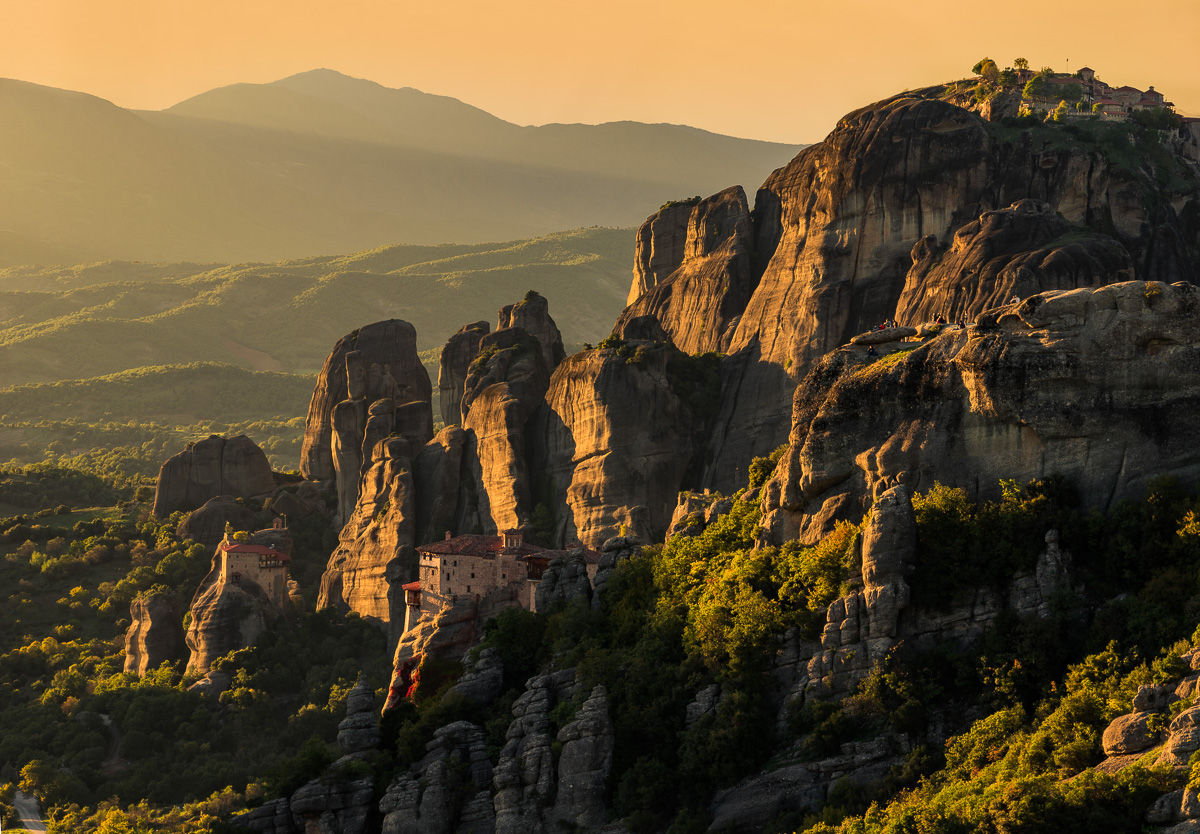 The last sunlight of the day on 3 monasteries and the huge walls of Meteora