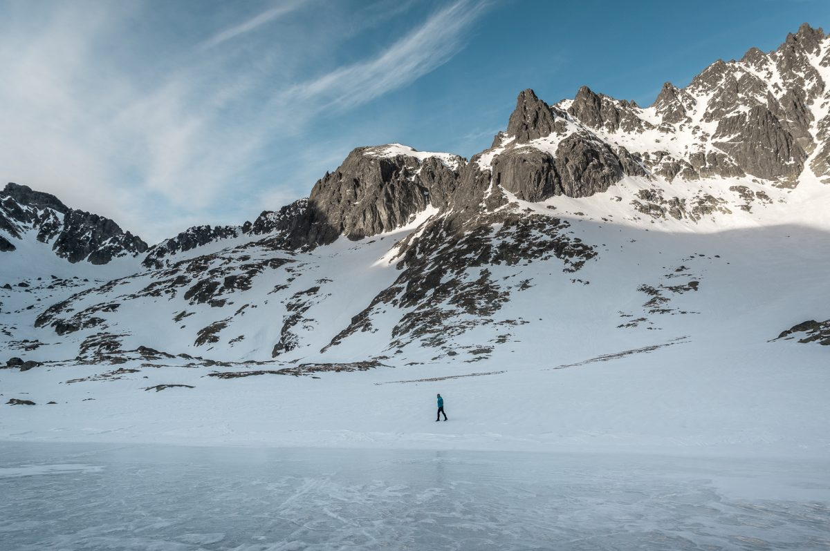 A hiker walking on the shore of a frozen lake